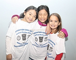 A photo of three young girls with arms around each other wearing white Operation Code Blue t-shirts